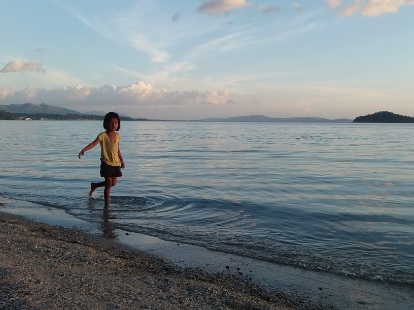 Little girl playing by the shore.